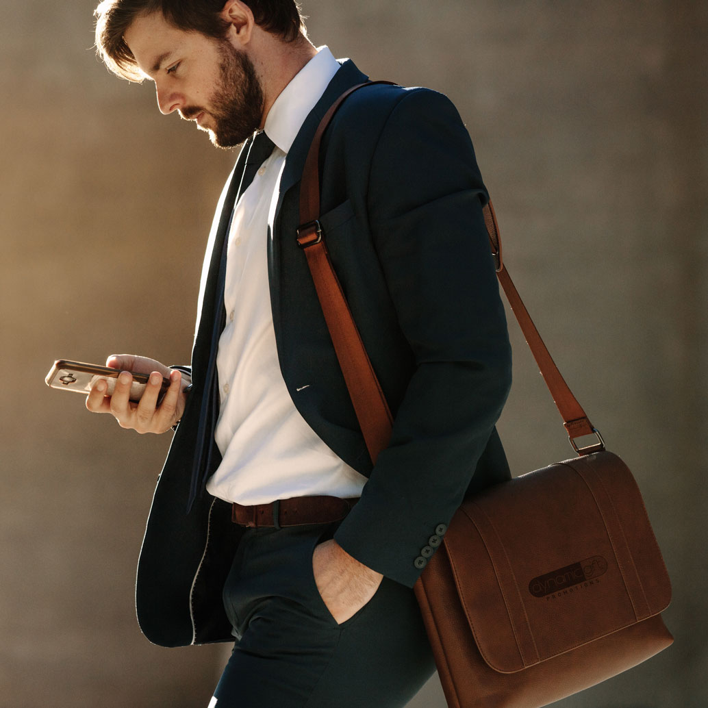 Business man carries branded bag while checking his phone