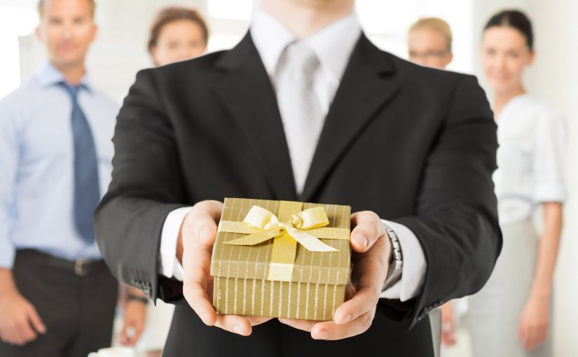 Business man hands over wrapped gift box to client
