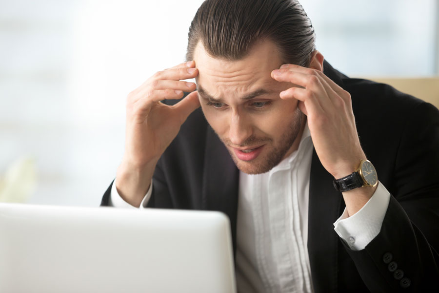 Frustrated man looking at laptop screen
