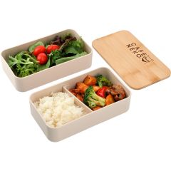 An angled view of a beige coloured stackable bento box unpacked to show two different layers side by side, both filled with food. Beside these is the boxes bamboo lid with laser engraving on it