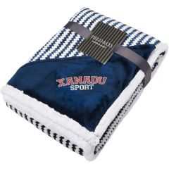 An angled view of a navy and white zig zag striped blanket folded up. In the corner there is a navy triangle of material with an embroidered logo on it