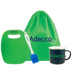 A green cutting board with a blue logo beside a lue and white basting brush with a blue logo. Beside these there is a green drawstring bag with a blue logo and a dark blue mug with a green logo