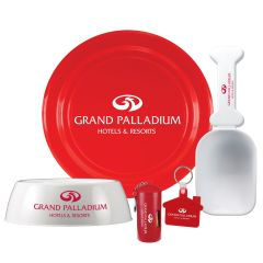 A white dog bowl with a red logo beside a bag dispenser with a white logo. Behind this is a red flyer with a white logo and a white scoop with a bone shaped handle and a red logo. Infront of this to the left is a red house shaped keyring with a white logo