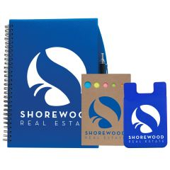 A blue journal with a white logo next to a natural coloured sticky note set with a blue logo and a blue silicone cellphone sleeve with a white logo next to that