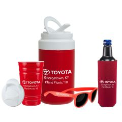 An uncapped red stadium cup with a white logo and lid beside ared and white cooler jug that also has a white logo. Beside these are a pair of orange shades with a white logo and a red drink koozie with a white logo and a bottle inside it