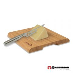 An angled view of a bamboo cutting board with a laser engraved logo. On the board is a cheese cutter knife partially inside a block of cheese
