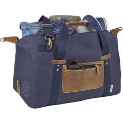 """An angled view of a navy cotton canvas and vinyl 20"""" duffle bag that is open at the top to show the contents stored within. The bag also has a debossed logo on the front"""