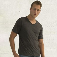 A charcoal heather coloured ring spun V-neck tee being worn by a short haired man with one hand in his pocket standing in front or a grey wall