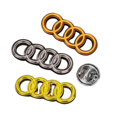 three moulded and polished lapel pins shaped like interlocking rings each a different metal beside a butterfly lapel pin button