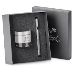 silver and black wireless speaker and pen in gift box with lid half hidden behind it