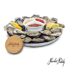 A stainless steel oyster tray filled with oysters and with a dipping sauce bowl in the center. In front of the tray there is a wooden lid with a logo on it