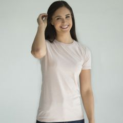 A dawn coloured cotton and polyester round neck T-shirt bring worn by a woman with long dark hair stood with one arm raised