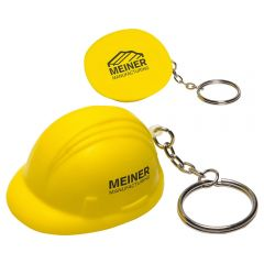 Two yellow coloured hard hat shaped stress relievers with silver coloured metal keychains and split ring attachments. The nearest hat is upright and has a black logo on the side. The hat behind it is turned to show the base with a black logo