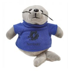 """The front view of a 6"""" seal plush wearing a blue T-shirt with a black logo on it"""