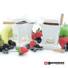 A ten piece white chocolate fondue set uncluding two bowls, two ceramic bases and four forks with wooden handles. The bowls are filled with chocolate and surrounded by fruit
