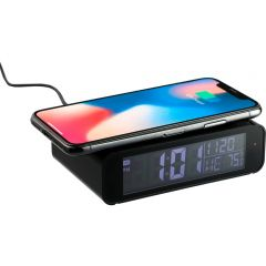 An angled front view of a black retro style clock with a smart phone on top