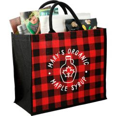 An angled view of a red plaid jute tote with a white logo, black sides and handles and filled with goods