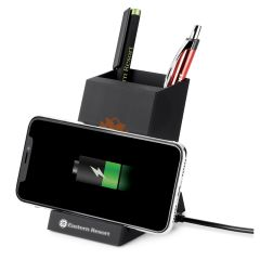 A black 2-in-1 pen holder and wireless charger with a smartphone resting horizontally on the front above its white logo and there are pens stored inside the holder