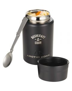 A black coloured cylindrical copper insulated food storage container with an engraved logo, uncapped with the lid beside it, the spoon propped against it and filled with food
