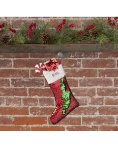 A red and green reversible sequin holiday stocking with a red and black logo on the white trim. The stocking is filled with gifts and hung on a brick and wood mantlepiece