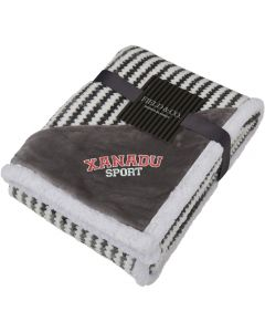 An angled view of a grey and white zig zag striped blanket folded up. In the corner there is a grey triangle of material with an embroidered logo on it