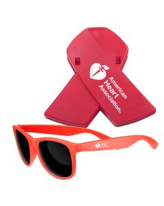 An orange set of shades with a white logo in front of a red plastic ribbon magnet clip with a white logo