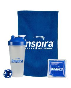 A frosted fitness shaker bottle with a blue lid and logo and the blue shaker part beside it. Behind this is a blue rally towel with a white logo next to a small blue gel pack with a white logo
