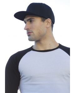 A man wearing a white and black baseball t-shirt and a dark coloured flexfit snapback cap