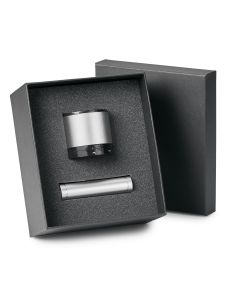 silver wireless speaker and powerbank in dark grey open gift box with lid half hidden behind it