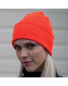 An orange coloured acrylic knit toque being worn by a blonde haired woman with pink lipstick
