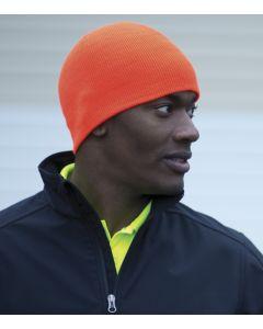 A man in a dark blue athletic jacket wearing an orange knit skull cap
