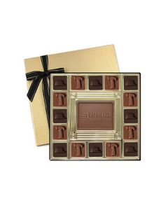 A gold coloured square gift box that is open to show the mixture of dark and milk chocolate molded squares that frame the edges of the inside of the box. In the center of these is a custom molded milk chocolate bar. Behind the box is its gold lid with