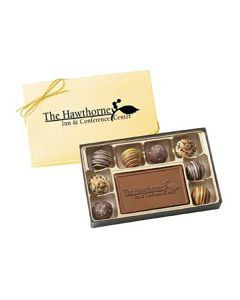 An open gift box filled with 8 assorted truffles and a milk chocolate custom molded bar in the center. Behind the box and half hidden is the boxes gold coloured lid with a matching bow and a black logo