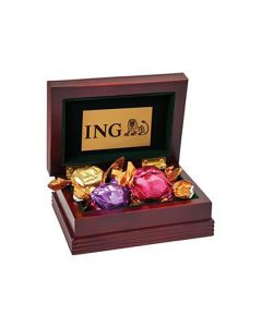 A mahogany coloured wooden box that is open to show the chocolate stored inside. The chocolate is wrapped in different coloured wrappers. On the interior of the open lid of the box is a brass coloured plate with a black logo on it