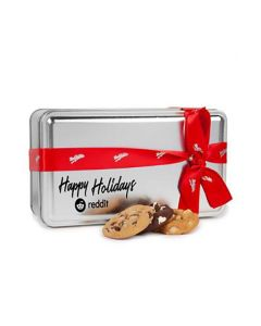 The front, angled view of a silver coloured rectangular tin with a red and white ribbon and a black logo on the front. In front of the tin are three assorted cookies