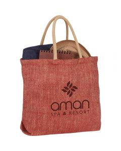 A maroon herringbone pattern jute tote with a brown logo light brown handles and filled with goods